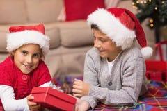 Frère et soeur se trouvant sur la couverture tenant un cadeau Photographie stock libre de droits