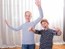 Frère et soeur souriant et ondulant avec leurs mains Photographie stock