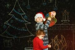 Frère et soeur sur le fond de Noël, jouant avec une palette et des brosses Joyeux Noël Images libres de droits