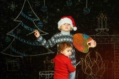 Frère et soeur sur le fond de Noël, jouant avec une palette et des brosses Joyeux Noël Photos libres de droits