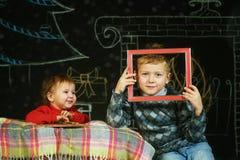 Frère et soeur sur le fond de Noël, jouant avec une palette et des brosses Joyeux Noël Photos stock