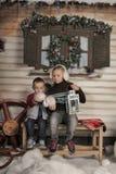 Frère et soeur sur un banc devant la maison en hiver Photos stock