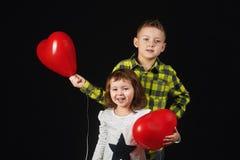 Frère et soeur tenant des ballons Images stock