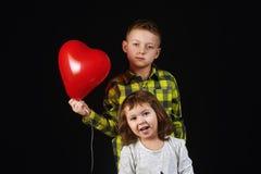 Frère et soeur tenant des ballons Image stock