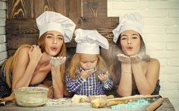 Frère et soeurs soufflant la farine Image stock