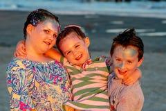Frère et soeurs sur la plage au coucher du soleil pendant l'heure d'or Photographie stock