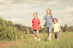 Frère heureux et soeurs courant sur la route au temps de jour Image stock