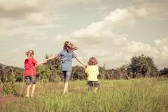 Frère heureux et soeurs courant sur la route au temps de jour Photographie stock libre de droits