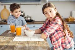 Frère inspiré et soeur prenant le petit déjeuner sain Photo stock