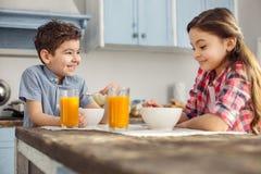 Frère joyeux et soeur prenant le petit déjeuner sain Image stock