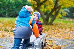 Frère poussant la voiture pour l'enfant Bonheur, amusement, loisirs en parc de chute Photographie stock