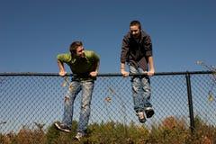 Frères climing une frontière de sécurité Photographie stock libre de droits
