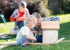 Frères d'enfants faisant la volière ensemble sur la pelouse dans l'été Photographie stock