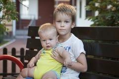 Frères d'enfants s'asseyant sur le banc Photographie stock