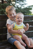 Frères d'enfants s'asseyant sur le banc Photographie stock libre de droits
