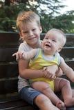 Frères d'enfants s'asseyant sur le banc Photo libre de droits