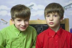 Frères de jumeaux heureux restant au mur Photos stock