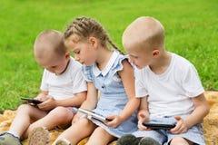 Frères et soeur à l'aide des smartphones Image stock