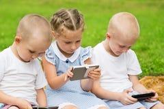 Frères et soeur employant se reposer de smartphones Photos libres de droits