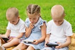 Frères et soeur employant se reposer de smartphones Image stock