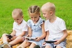Frères et soeur heureux à l'aide des smartphones Photo libre de droits