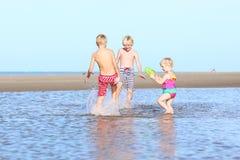 Frères et soeur jouant sur la plage Image libre de droits