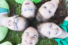 Frères et soeurs se trouvant sur l'herbe Photos stock