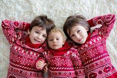 Frères heureux, bébé et enfants d'école maternelle, étreignant à la maison sur la couverture blanche, souriant photographie stock