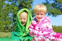Frères heureux dehors en serviettes de plage Images stock