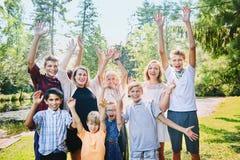Frères heureux et soeurs ou amis soulevant des bras Photographie stock