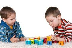 Frères jouant des blocs sur le tapis Photos stock
