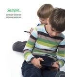 Frères jouant des jeux vidéo sur des comprimés Photographie stock libre de droits