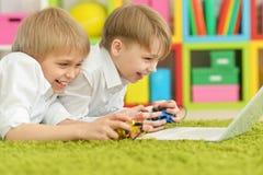 Frères jouant un jeu d'ordinateur Photo stock