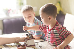 Frères jumeaux aidant sa mère à rectifier le café Images stock