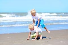 Frères jumeaux jouant sur la plage Image stock