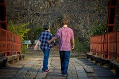 Frères marchant sur un pont Photo stock