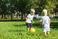 Frères mignons jouant avec une boule ensemble dans le jardin photos libres de droits