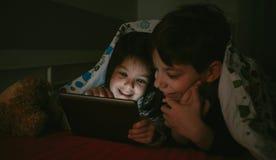 Frères regardant le comprimé dans l'obscurité Image libre de droits