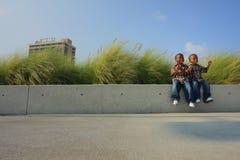 Frères s'asseyant sur une saillie photographie stock libre de droits
