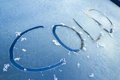 Frío de la palabra escrito en el parabrisas escarchado Foto de archivo libre de regalías