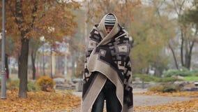 Frío de sensación del hombre enfermo desamparado, vagando en el parque de la ciudad cubierto con la manta vieja almacen de metraje de vídeo