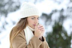 Frío sufridor de la mujer al aire libre en un invierno nevoso Imagenes de archivo