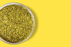 Frö av sur frukt för passionfrukt, högt vitamin C i en klar handfat, på gul bakgrund med kopieringsutrymme för text arkivfoton