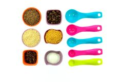 Frö kryddor, korn i små mång--färgade koppar och mätaskedar Fotografering för Bildbyråer