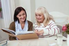 Fröhliche ältere Frau und Pflegekraft, die Fotoalbum nachforscht stockbild