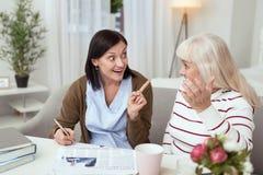 Fröhliche ältere Frau und Pflegekraft, die Kreuzworträtsel löst stockfotos