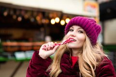 Fröhliche Blondine in der roten Strickmütze, die mit Zuckerstange an aufwirft Lizenzfreie Stockfotografie
