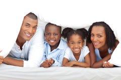 Fröhliche Familie, die Spaß hat, auf Bett sich hinzulegen Stockfotografie