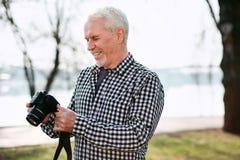 Fröhliche Festlegungskamera des älteren Mannes lizenzfreie stockbilder