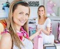 Fröhliche Frau, die Einkaufenbeutel von der Verkäuferin erhält Stockbild
